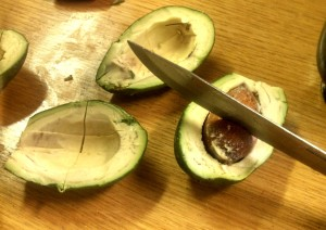 Cut avocado in half then remove the pit using your knife and twisting out the seed