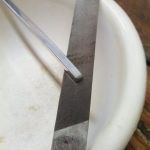 Cut to length and then file of the top edge to its final angle and the bottom edge to a circle.  If you don't you will start upset then end of the material and start cracks.