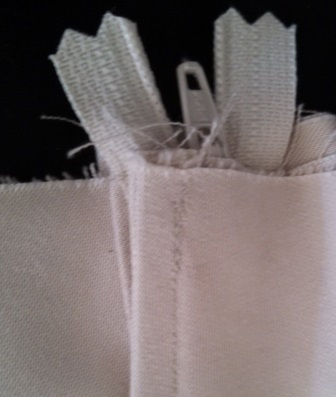 After some failures in previous zipper attempts, I also learned that the zipper should be installed so that the raw edges are above the edge of the fabric. That way, they'll be inside the waistband.
