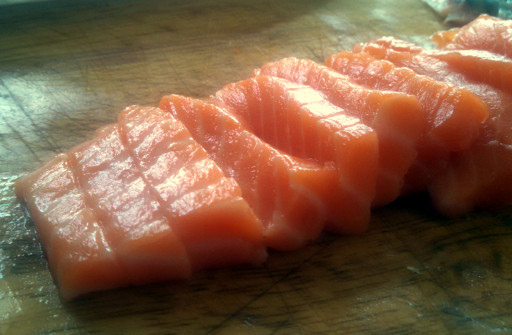 Thinly sliced. A sharp knife an even medium pressure is necessary to cut raw salmon crisply.